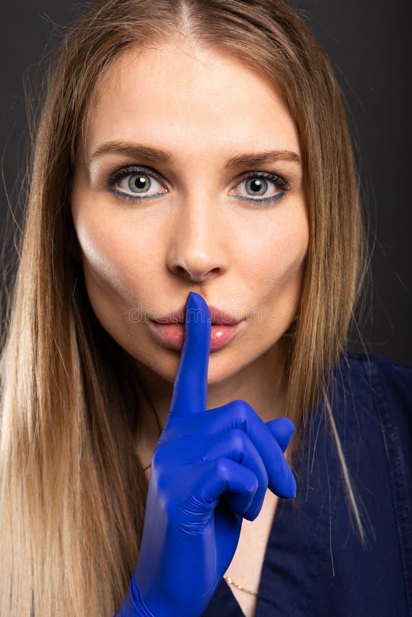 Plan rapproché de docteur féminin faisant le geste silencieux d'audition photographie stock libre de droits