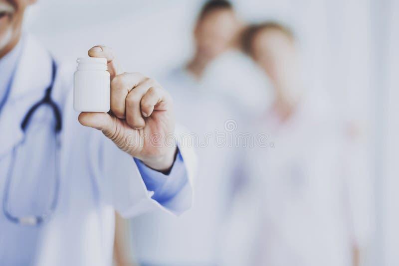 Plan rapproché de docteur Hand avec montrer le pot avec la drogue image libre de droits