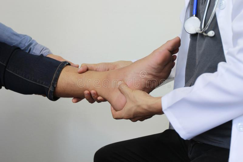 Plan rapproché de douleur se sentante de l'homme dans son pied et docteur le traumatol photographie stock