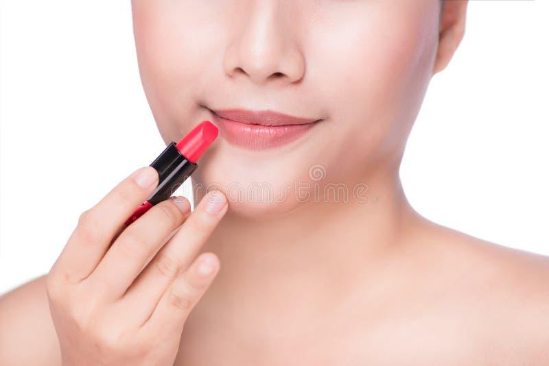 Plan rapproché de femme asiatique appliquant le rouge à lèvres rouge sur des lèvres photographie stock