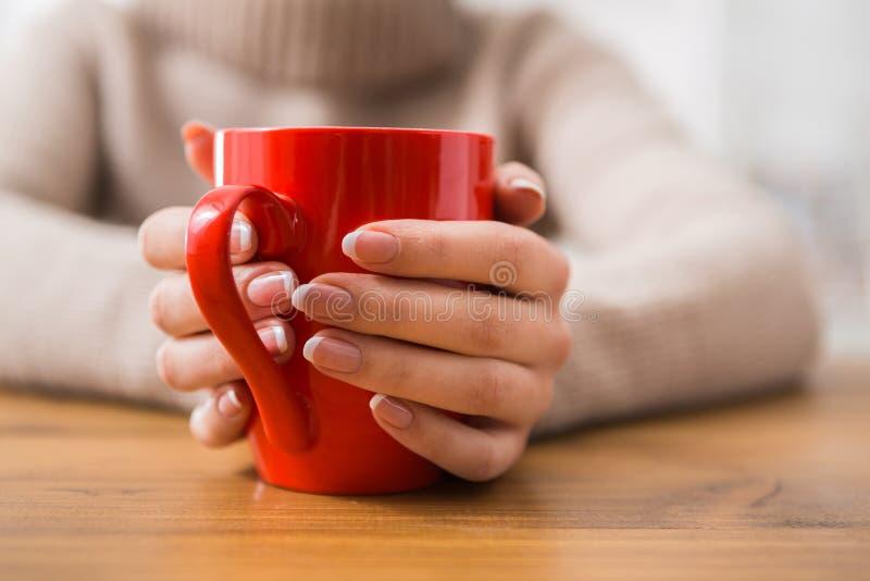 Plan rapproché de femme avec la tasse de la boisson chaude photo libre de droits
