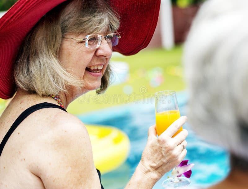 Plan rapproché de femme caucasienne supérieure avec du jus par la piscine photos stock