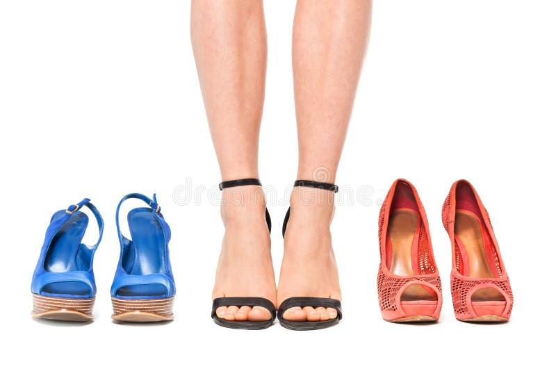 Plan rapproché de femme choisissant une paire de chaussures - d'isolement sur le blanc image libre de droits