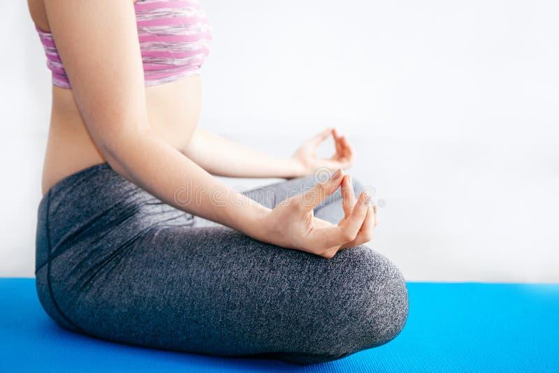 Plan rapproché de femme faisant la méditation de yoga dans des WI de position de pose de lotus photos stock
