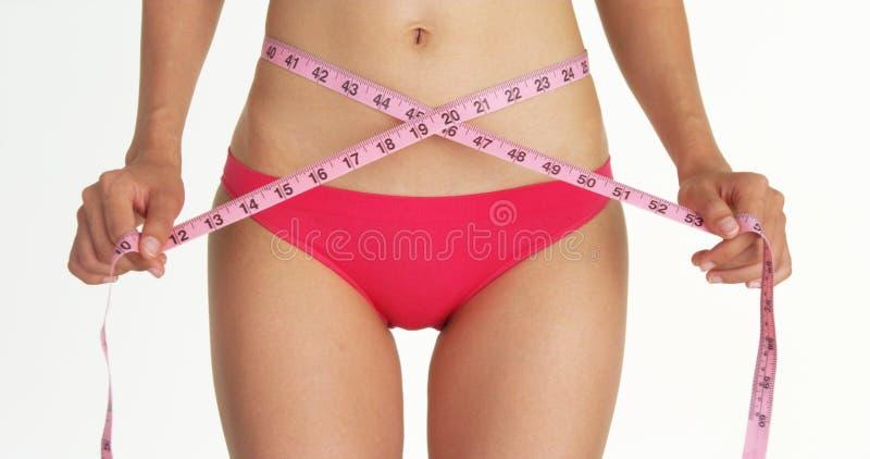 Plan rapproché de femme mesurant sa taille avec la bande image libre de droits