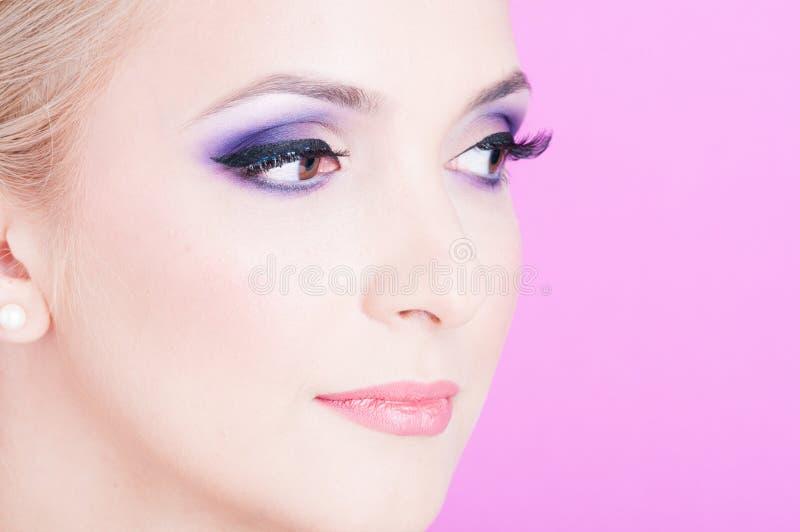 Plan rapproché de femme posant en tant que maquillage de professionnel de beauté photographie stock