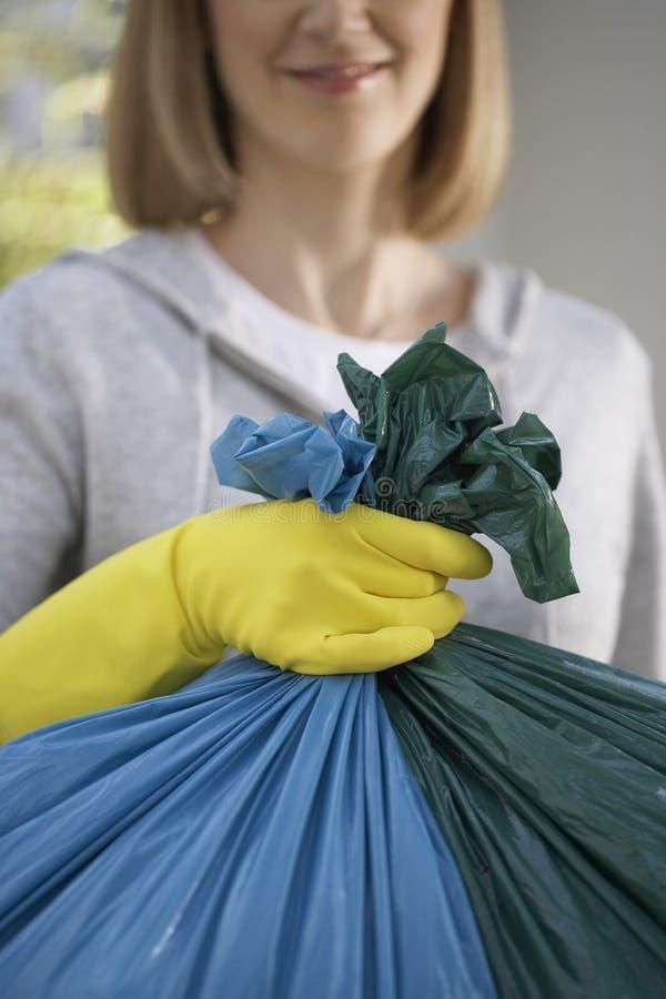 Plan rapproché de femme tenant le sac de déchets image stock