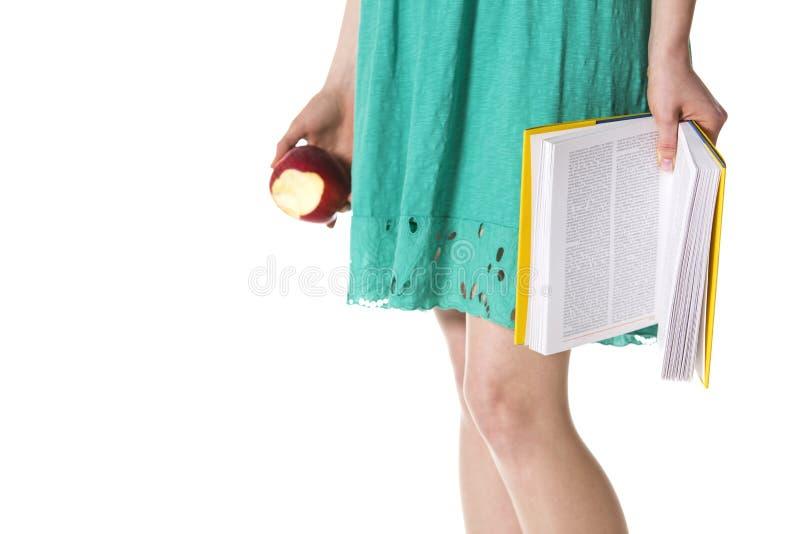 Plan rapproché de fille avec le livre et la pomme. photographie stock libre de droits