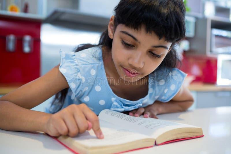 Plan rapproché de fille se dirigeant tout en lisant le roman dans la cuisine photo libre de droits