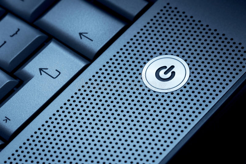 Plan rapproché de foyer sélectif d'ordinateur portable bleu argenté d'ordinateur sur l'idéal de réserve de bouton ON pour le symb photo libre de droits