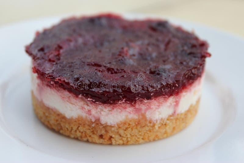 Plan rapproché de gâteau au fromage crémeux avec le bonbon à baie sur le dessus image stock