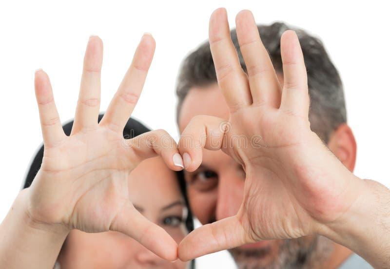 Plan rapproché de geste de coeur fait par des couples photo stock
