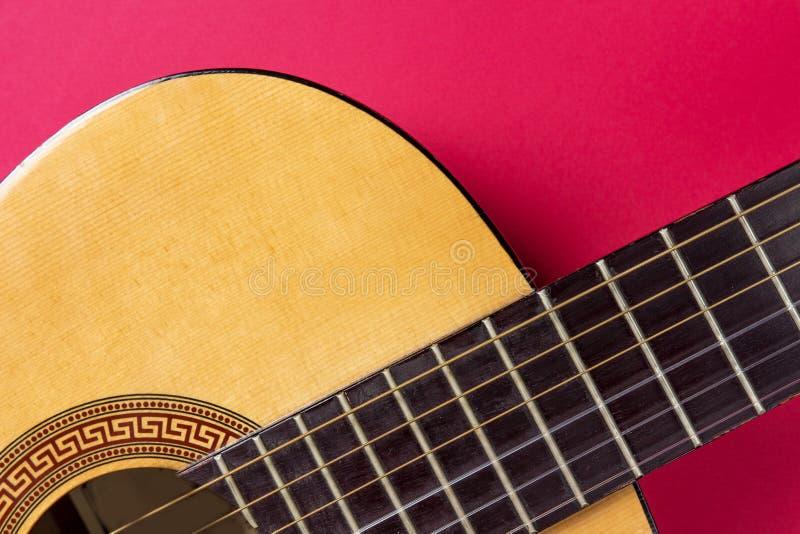 Plan rapproché de guitare acoustique sur un fond rose Concept de passe-temps de musique photographie stock libre de droits
