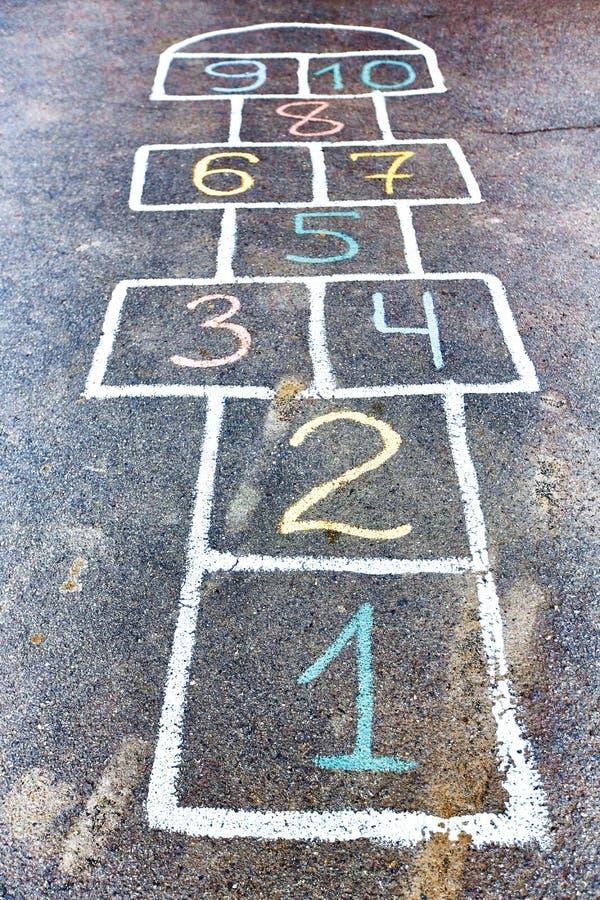 Plan rapproché de jeu de marelle dessiné avec la craie sur la route goudronnée Enfants image libre de droits
