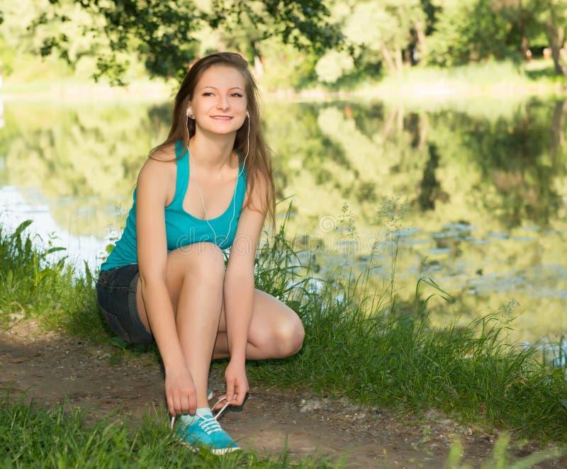 Plan rapproché de jeune femme attachant des dentelles de chaussure Forme physique femelle RU de sport photographie stock