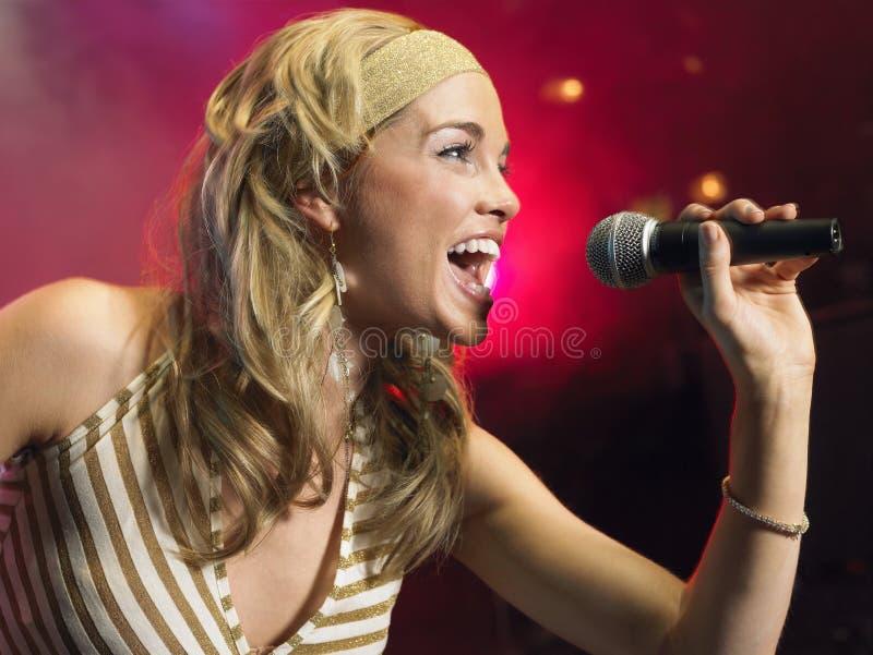 Plan rapproché de jeune femme chantant dans le microphone photo libre de droits