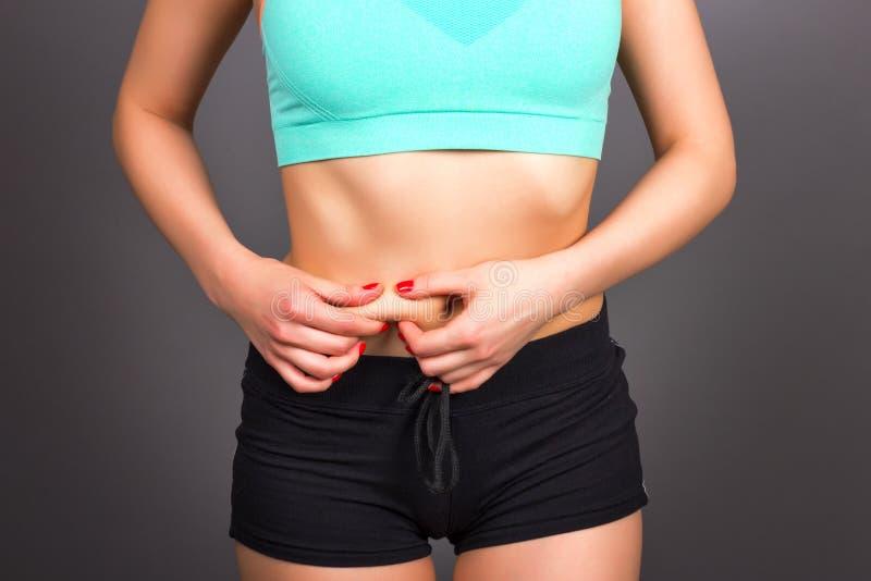 Plan rapproché de jeune femme d'ajustement vérifiant sa graisse de ventre, concept pour images stock