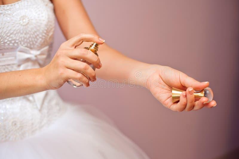 Plan rapproché de jeune jeune mariée étant prêt avec des parfums à la maison pendant le matin photographie stock libre de droits