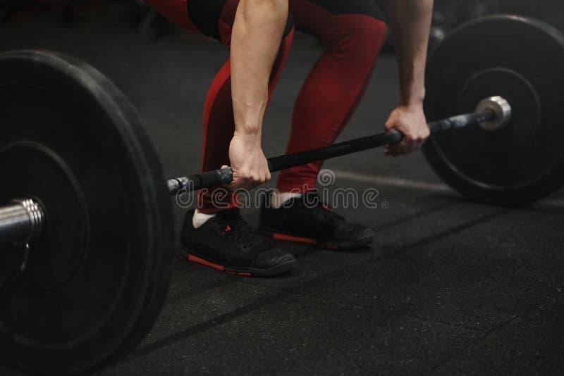 Plan rapproché de l'athlète féminin de crossfit se préparant aux poids de levage au gymnase image libre de droits