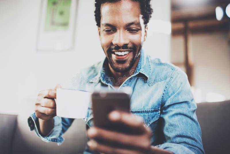 Plan rapproché de l'homme africain barbu de sourire faisant la conversation sur le smartphone à la maison moderne Personnes de co photo libre de droits