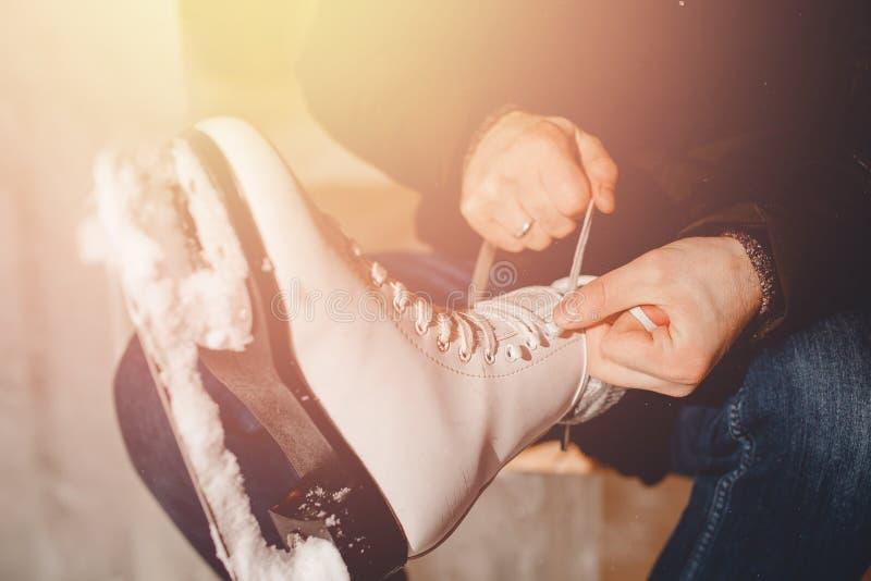 Plan rapproché de l'homme attachant des patins de dentelle sur la patinoire à la femme Couples de soin de concept dans l'amour images stock