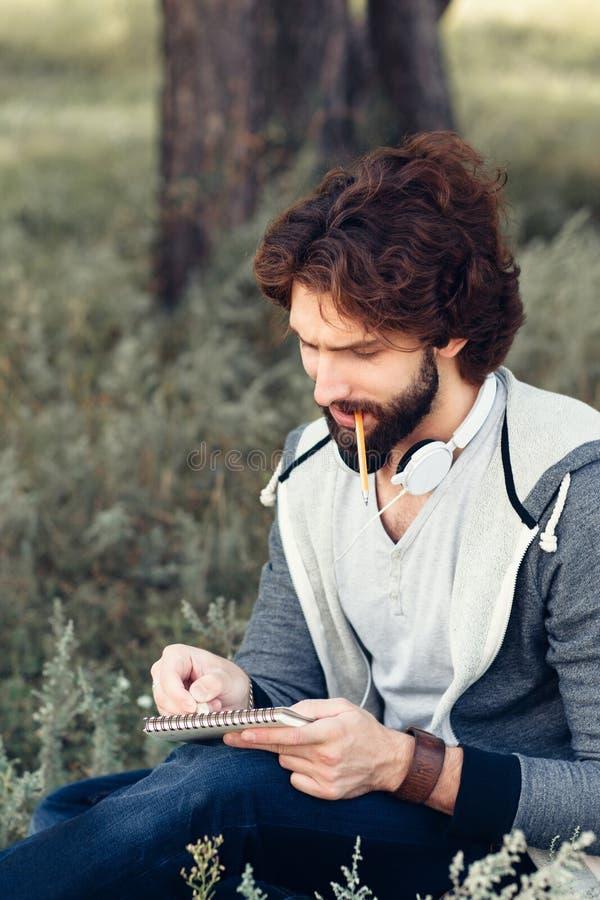 Plan rapproché de l'homme avec le crayon acéré de carnet photographie stock
