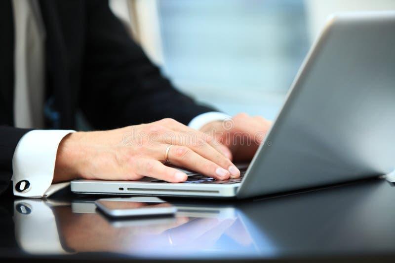 Plan rapproché de l'homme d'affaires de main à l'aide de l'ordinateur portable pour le travail au bureau image stock