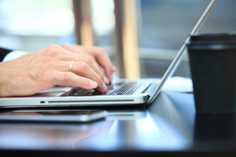 Plan rapproché de l'homme d'affaires de main à l'aide de l'ordinateur portable pour le travail au bureau photographie stock