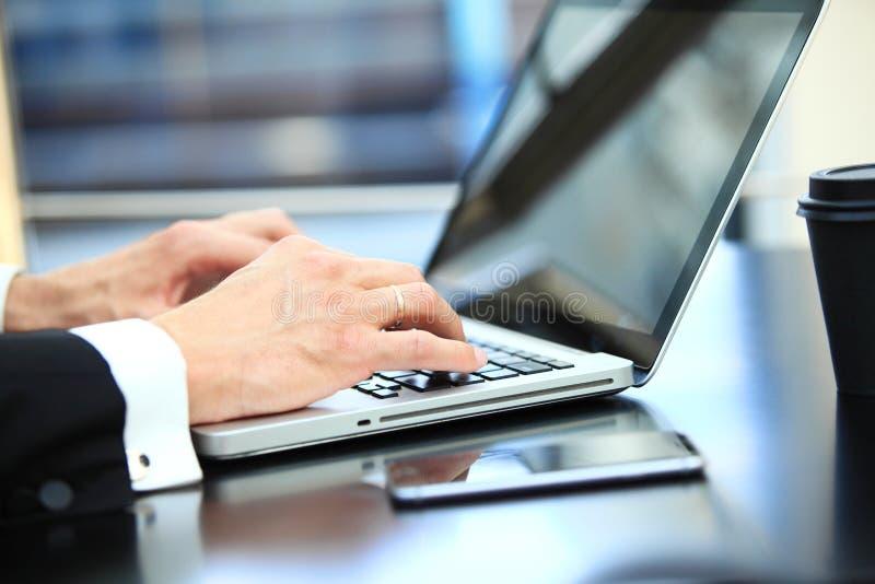 Plan rapproché de l'homme d'affaires de main à l'aide de l'ordinateur portable pour le travail au bureau photo libre de droits
