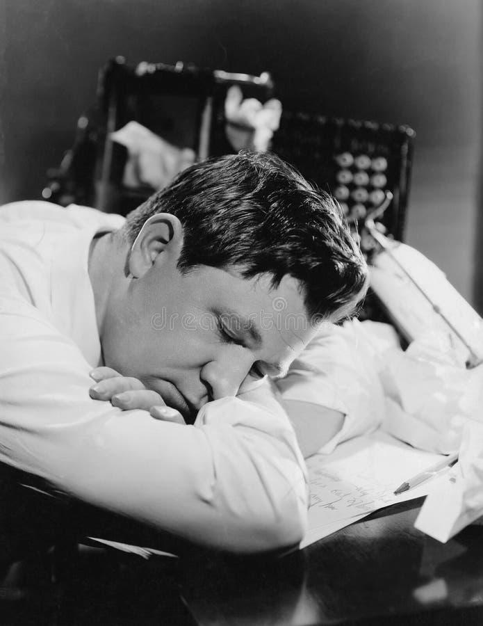 Plan rapproché de l'homme dormant à son bureau (toutes les personnes représentées ne sont pas plus long vivantes et aucun domaine photos stock