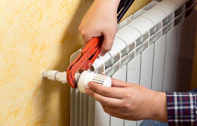 Plan rapproché de l'homme installant le radiateur de chauffage et reliant la valve photographie stock