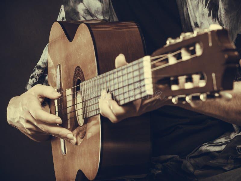 Plan rapproché de l'homme jouant la guitare acoustique photos stock
