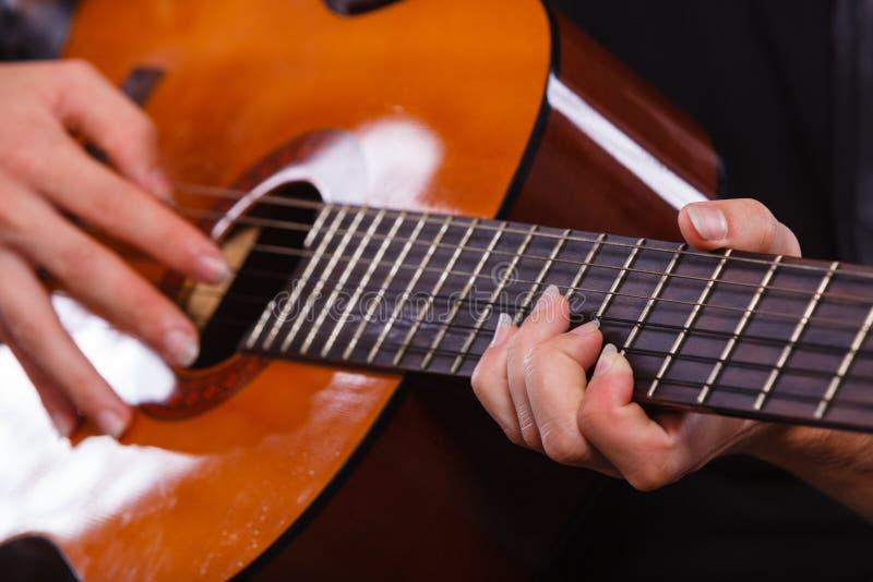 Plan rapproché de l'homme jouant la guitare acoustique photographie stock libre de droits