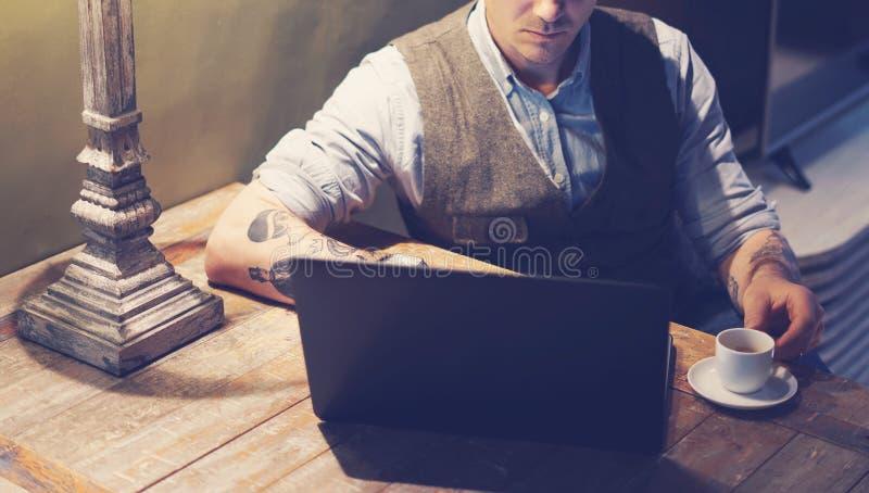 Plan rapproché de l'homme tatoué élégant travaillant à la maison sur l'ordinateur portable tout en se reposant à la table en bois images libres de droits