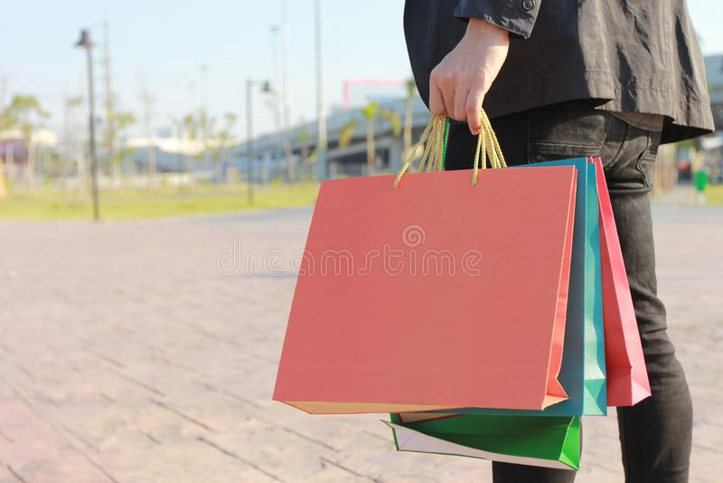 Plan rapproché de l'homme tenant des sacs à provisions avec la position au parking de voiture images libres de droits