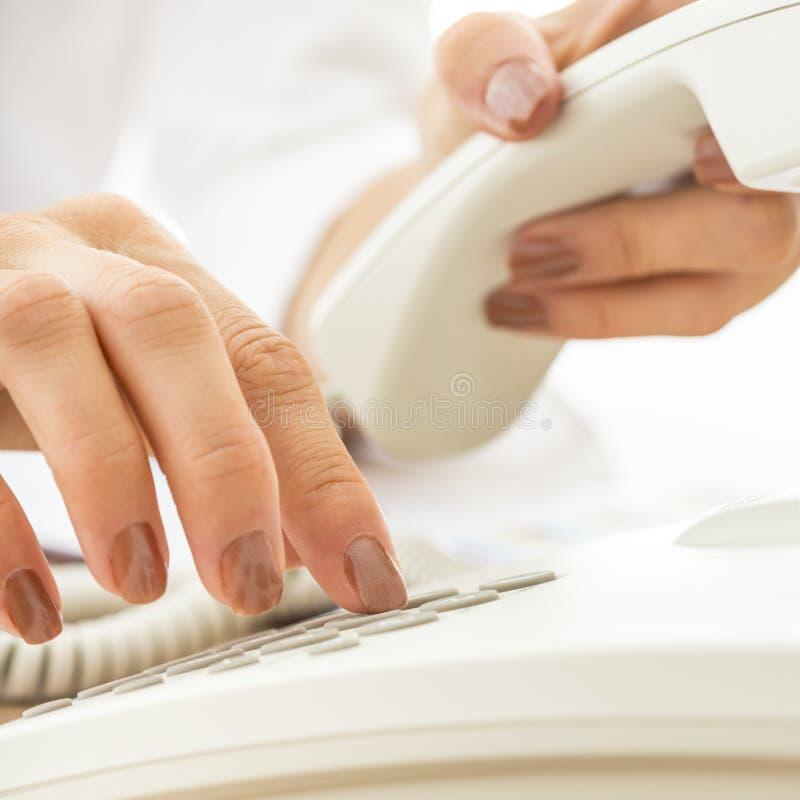 Plan rapproché de l'opérateur de téléphone féminin composant un numéro de téléphone images libres de droits