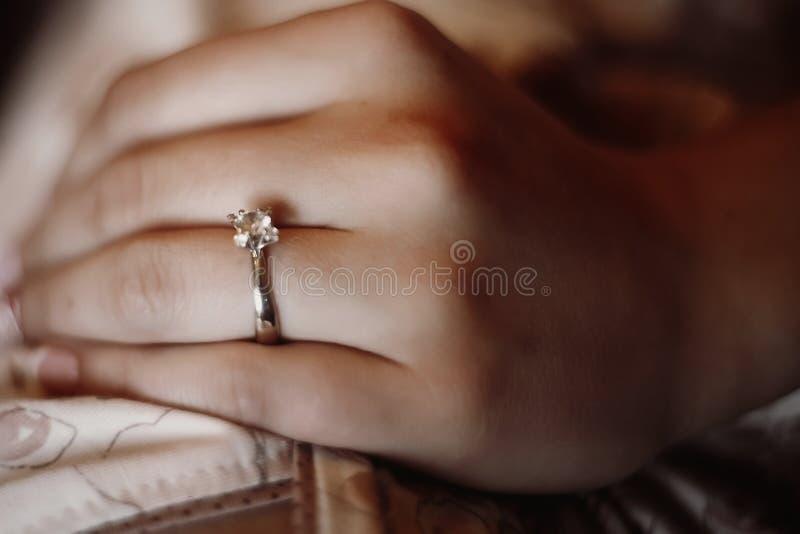 Plan rapproché de la bague de fiançailles argentée en main, belle jeune mariée dans le SI images stock