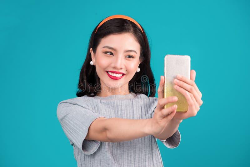 Plan rapproché de la belle fille asiatique de pin-up de sourire prenant la photo de selfie photos stock