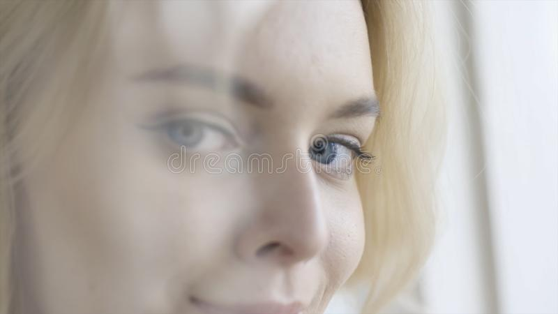 Plan rapproché de la belle jeune femme aux yeux bleus observant et souriant action Belle dame blonde avec les yeux bleus de charm photos stock