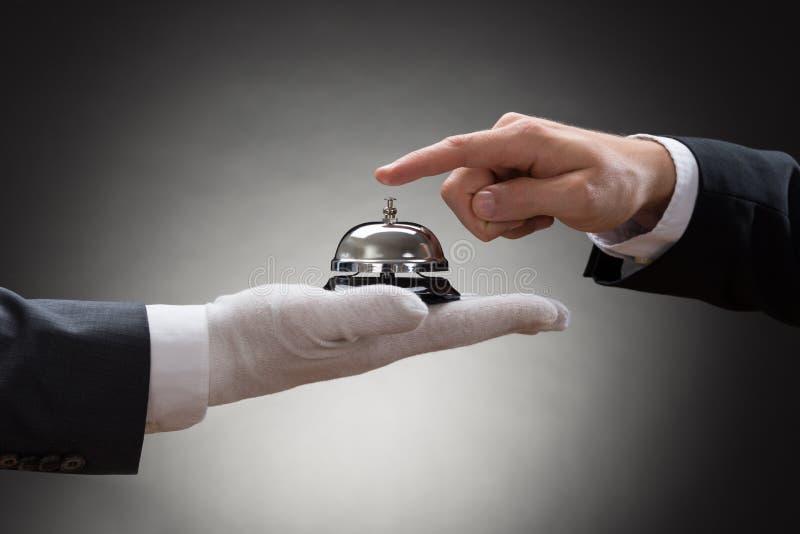 Plan rapproché de la cloche de sonnerie de service de la main d'une personne photographie stock