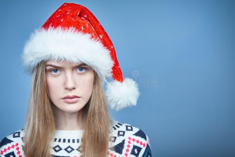Plan rapproché de la femme de froncement de sourcils fâchée utilisant le chapeau de Santa photographie stock libre de droits