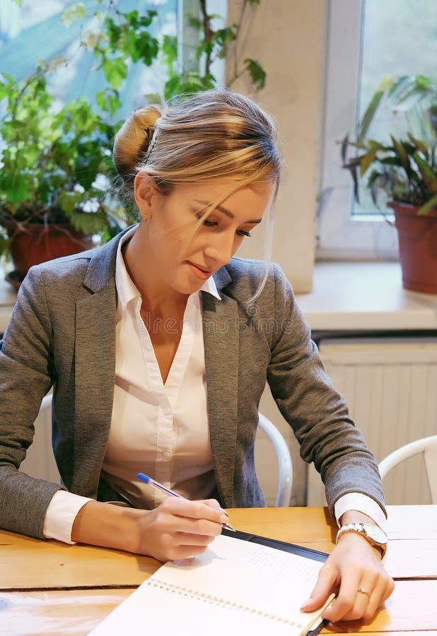 Plan rapproché de la jeune belle écriture de femme d'affaires dans le carnet images stock