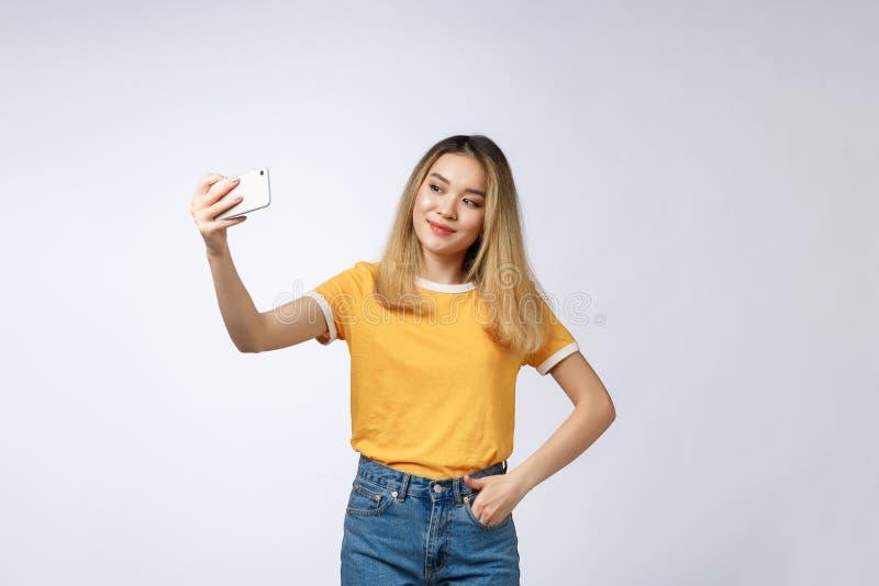 Plan rapproché de la jeune belle femme asiatique prenant le selfie Fond blanc d'isolement Beauté et femme en bonne santé images stock
