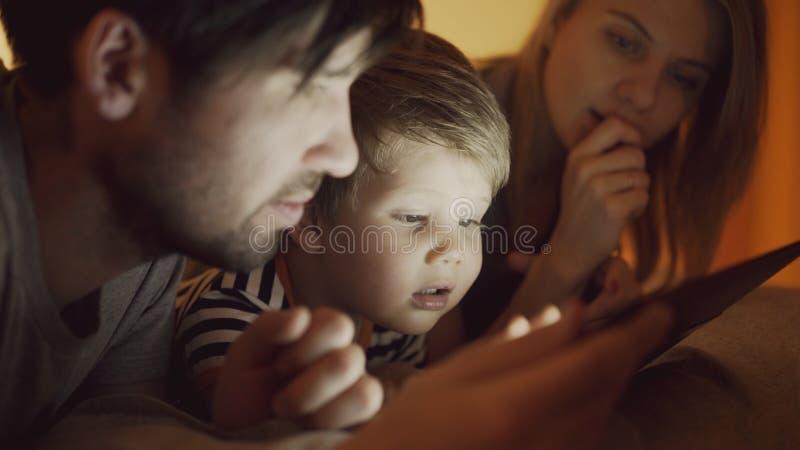 Plan rapproché de la jeune famille heureuse se situant dans le lit à la maison tandis que petit garçon apprenant à jouer la table images libres de droits