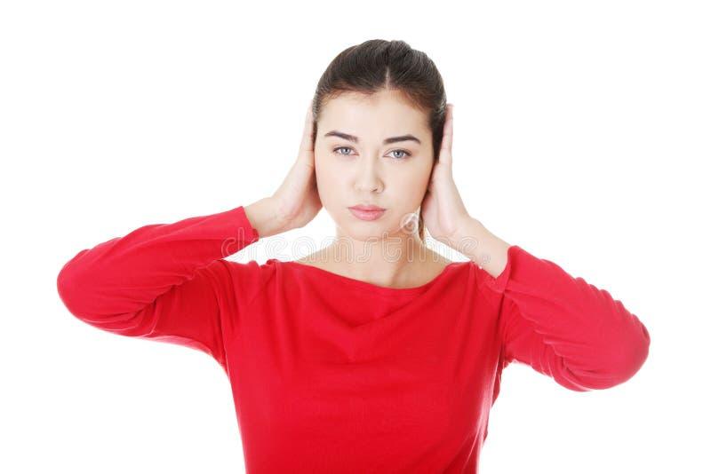 Plan rapproché de la jeune femme frustrante retenant ses oreilles photos libres de droits