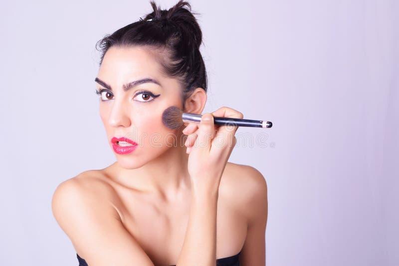 Plan rapproché de la jeune femme hispanique appliquant le maquillage photo stock