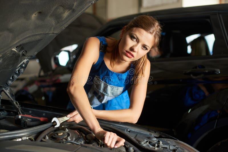 Plan rapproché de la mécanique féminine de brune réparant ou inspectant une voiture images stock