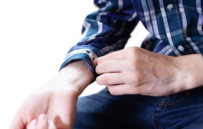 Plan rapproché de la main d'un homme élégant boutonnant sa manchette de chemise images libres de droits