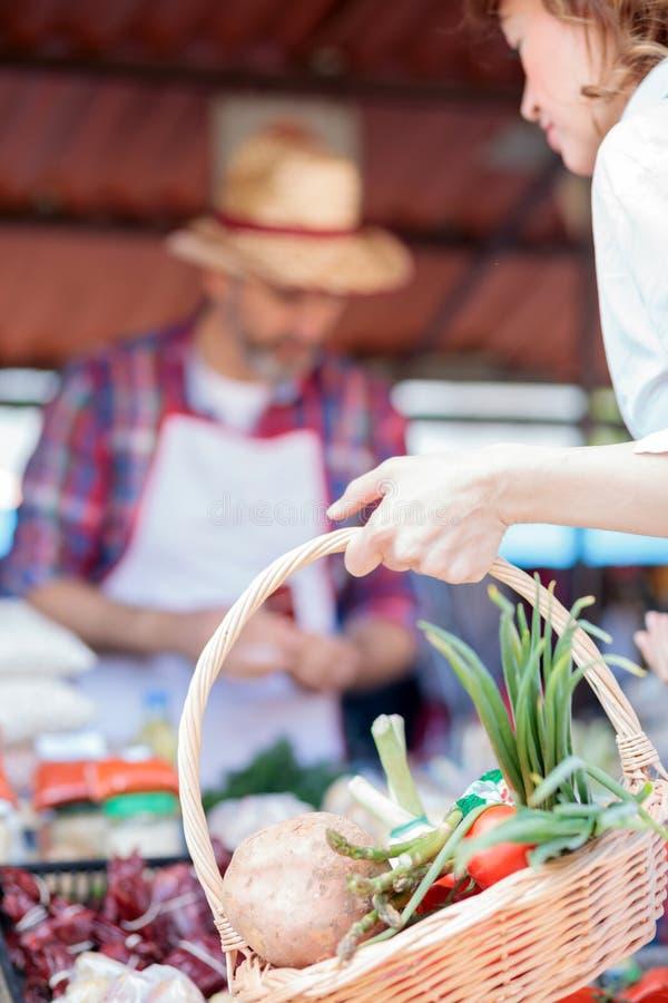 Plan rapproché de la main d'une femme tenant un panier à provisions complètement des légumes organiques frais images stock