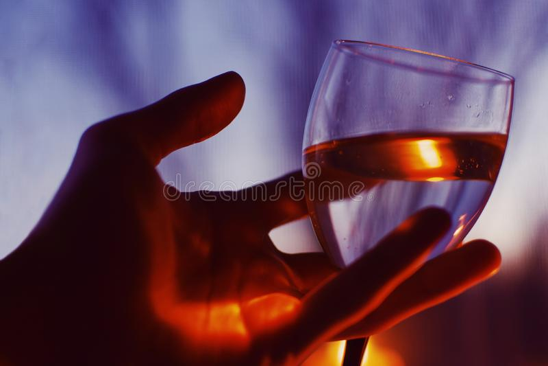 Plan rapproché de la main d'une personne tenant un verre de vin blanc avec un fond brouillé image libre de droits